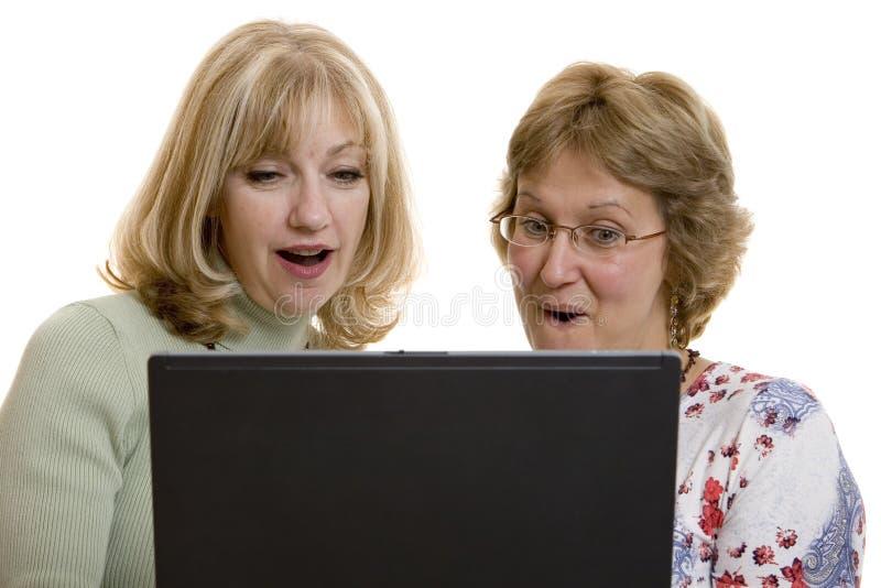 Femmes impressionnés regardant l'écran d'ordinateur photographie stock