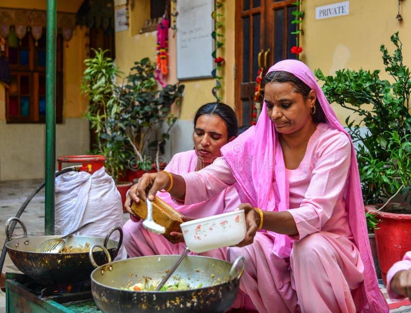 Femmes indiennes faisant cuire la nourriture traditionnelle image stock