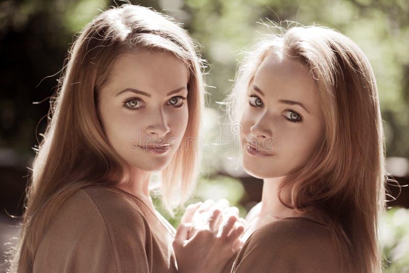 Femmes, jumelles dans la forêt images stock