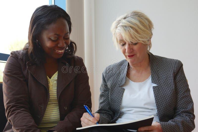 Femmes mûres noires et blanches travaillant ensemble image libre de droits