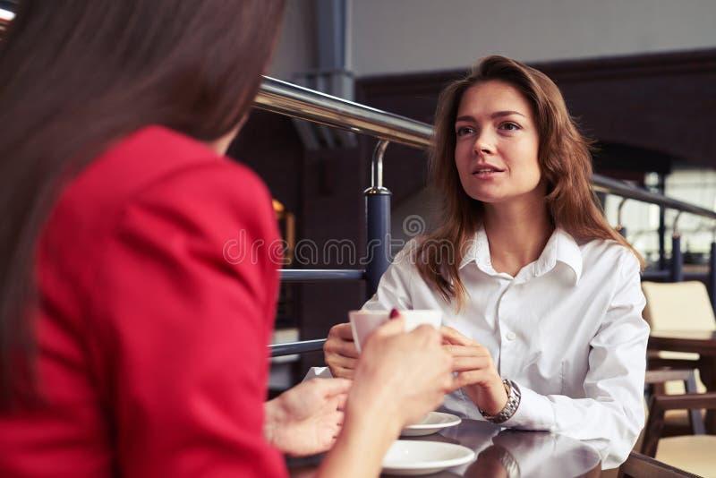 Femmes magnifiques d'affaires échangeant des vues tout en appréciant le café images stock