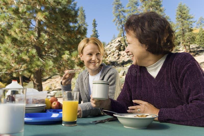 Femmes mangeant à la table de pique-nique dans le terrain de camping photos stock