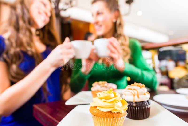 Femmes mangeant des petits pains tandis que boire de café photos stock