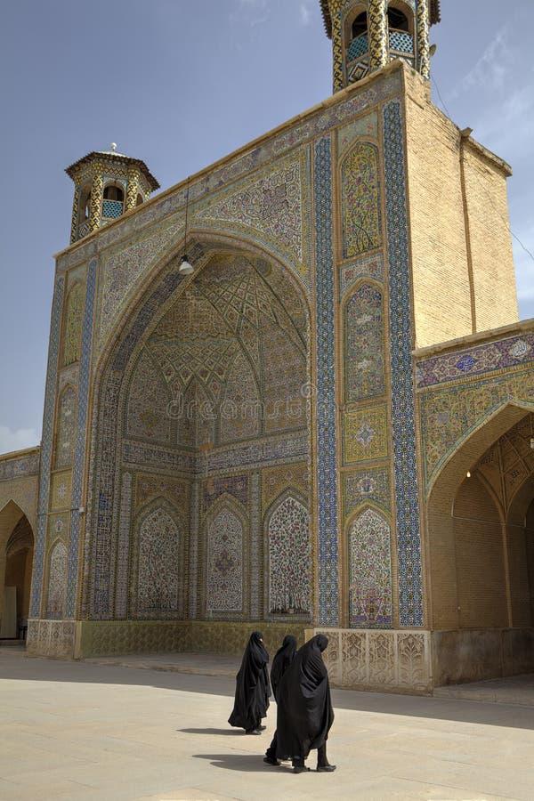 Femmes musulmanes portant le tchador noir dans la cour de la mosquée de Vakil images libres de droits