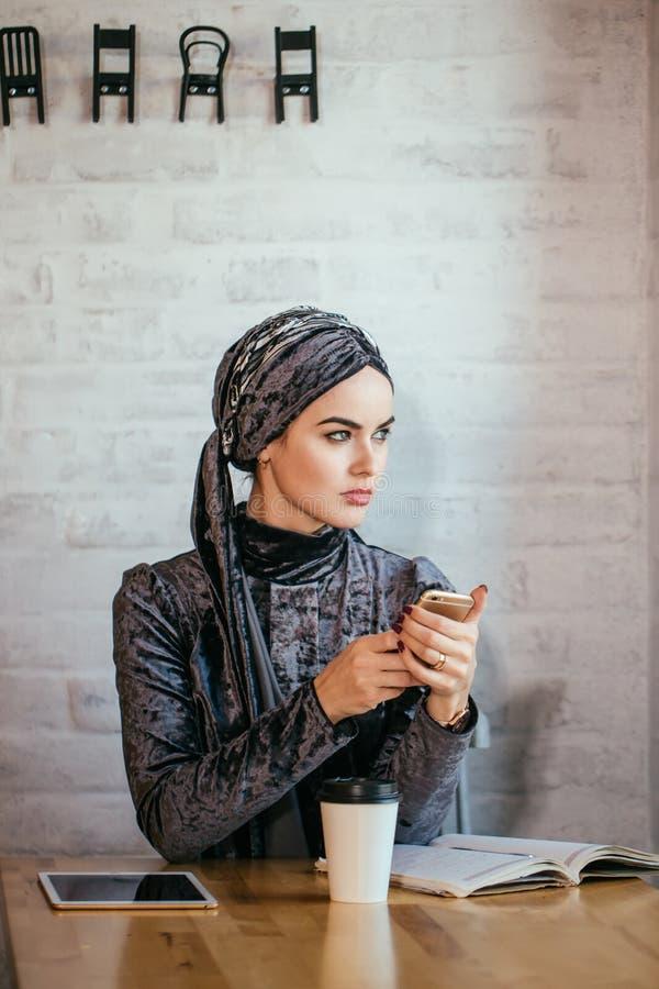 Femmes musulmanes tenant le smartphonephone pensée à de bons souvenirs images stock