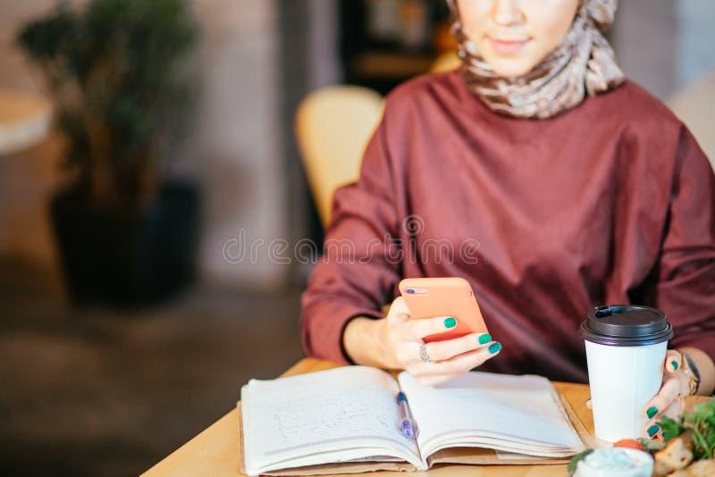Femmes musulmanes tenant le smartphonephone pensée à de bons souvenirs image stock