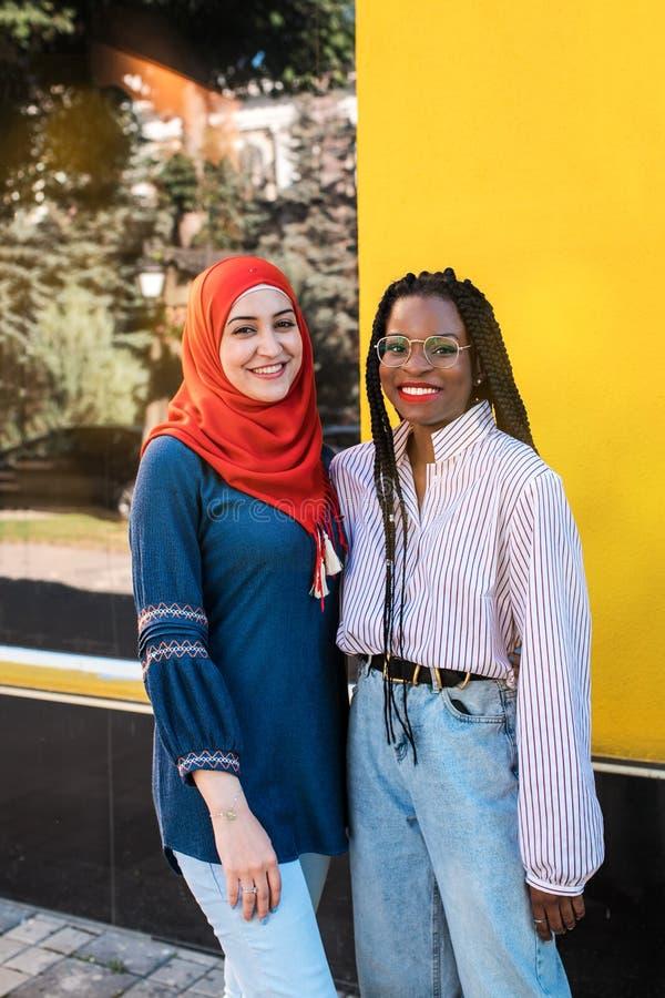 Femmes noires et musulmanes, meilleurs amis posant à la caméra à la rue photo stock