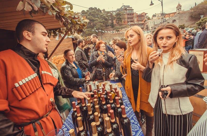 Femmes parlant du vin avec l'homme géorgien pendant le festival populaire Tbilisoba images stock
