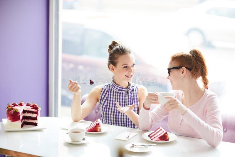 Femmes parlant et mangeant le gâteau en café images libres de droits