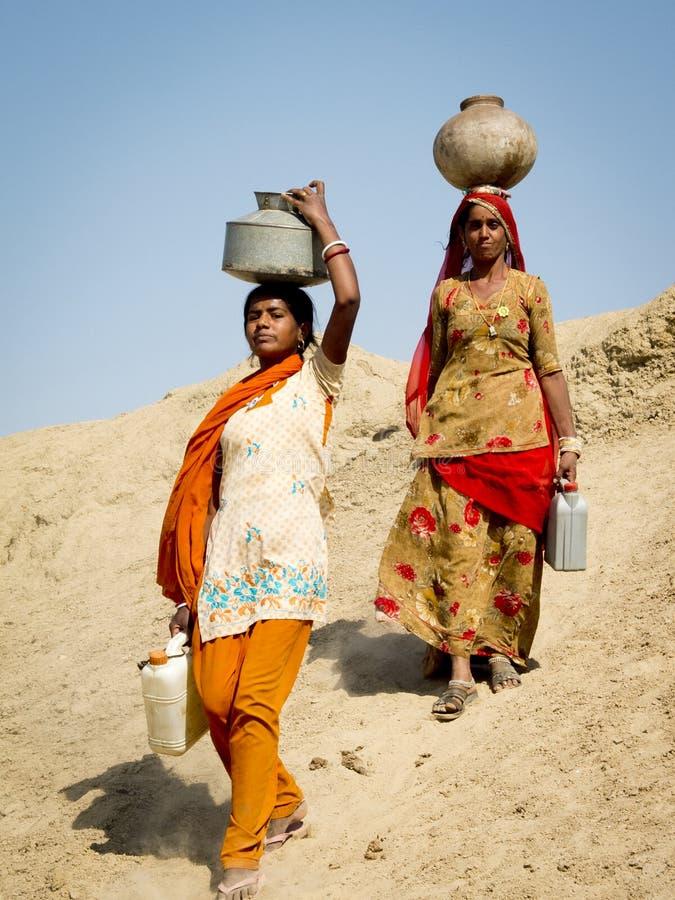 Femmes portant l'eau sur la tête. photo libre de droits