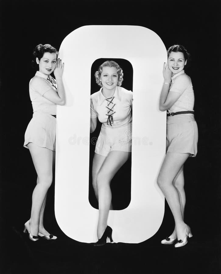 Femmes posant avec la lettre énorme O (toutes les personnes représentées ne sont pas plus long vivantes et aucun domaine n'existe image libre de droits