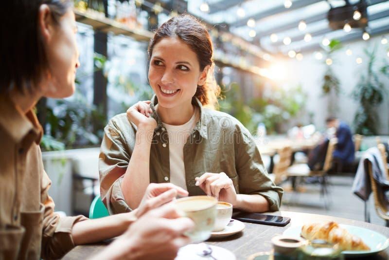 Femmes positives discutant des dernières nouvelles en café image libre de droits
