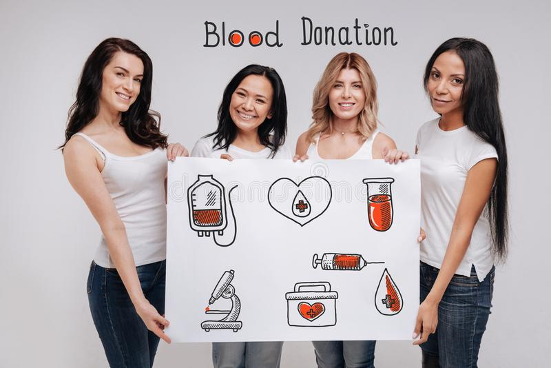 Femmes positives faisant participer des personnes dans le don du sang et le sourire images stock