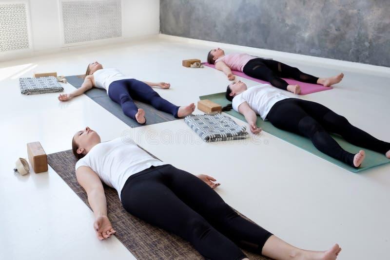 Femmes pratiquant la leçon de yoga, faisant le cadavre, Savasana, pose de cadavre d'exercice photos stock