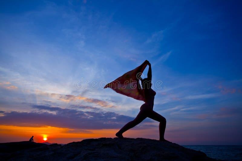 Femmes pratiquant le yoga au coucher du soleil images libres de droits