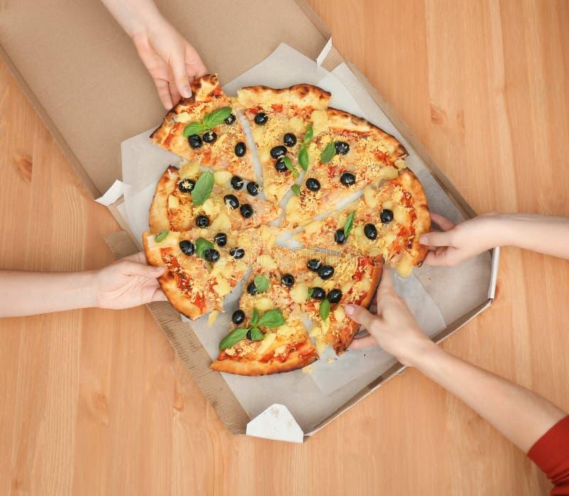 Femmes prenant des tranches de pizza italienne savoureuse de boîte sur la table en bois, vue supérieure photographie stock