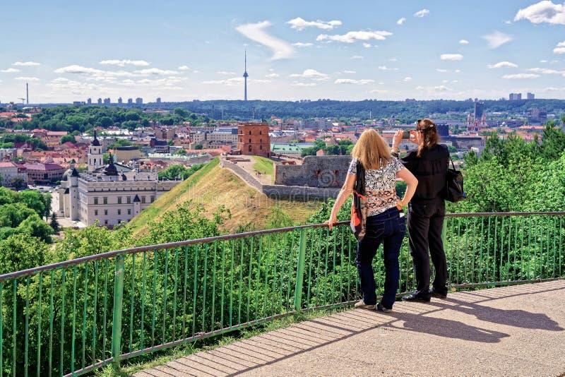Femmes prenant la photo de la tour et du château inférieur Vilnius de Gediminas photographie stock libre de droits