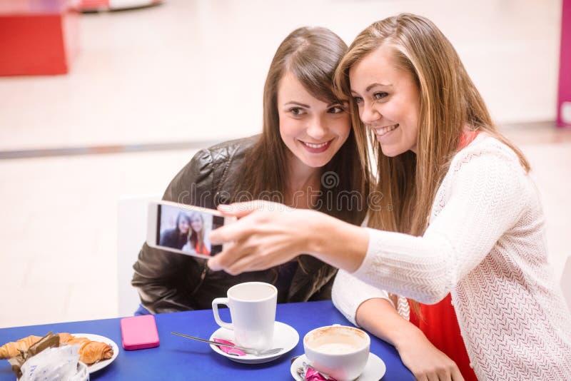 Femmes prenant un selfie tout en ayant le café images stock