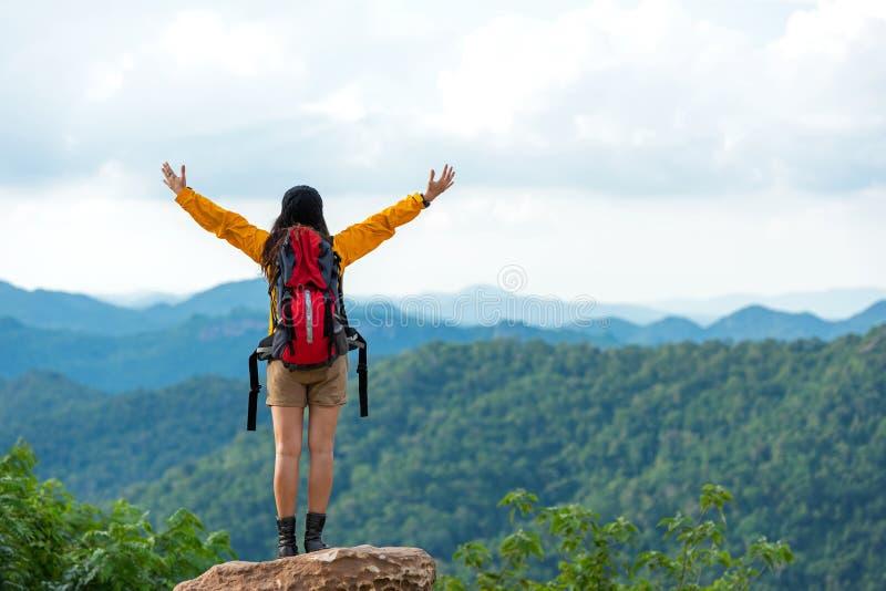 Femmes randonneur ou voyageuse avec l'aventure de sac à dos sentant le revêtement victorieux sur la montagne, extérieure pour la  images stock