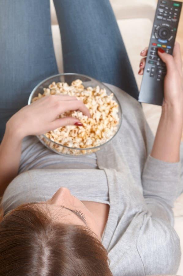 Femmes regardant la TV avec le maïs éclaté à la maison Vue supérieure photos libres de droits
