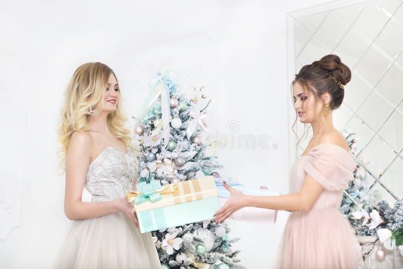 Femmes reportant des cadeaux par l'arbre de Noël images libres de droits