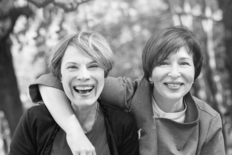 Femmes riantes étreignant et ayant l'amusement en parc, rétro portrait noir et blanc tonned photo stock