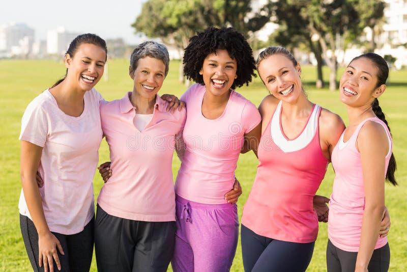 Femmes riantes portant le rose pour le cancer du sein image libre de droits