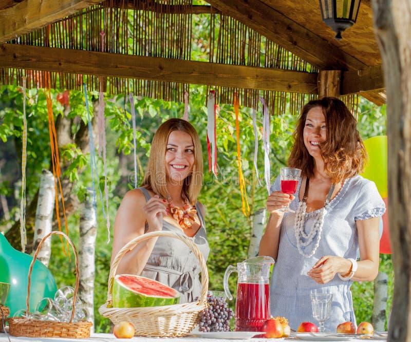 Femmes riantes près d'une table de fête avec un verre de vin dans des mains image libre de droits