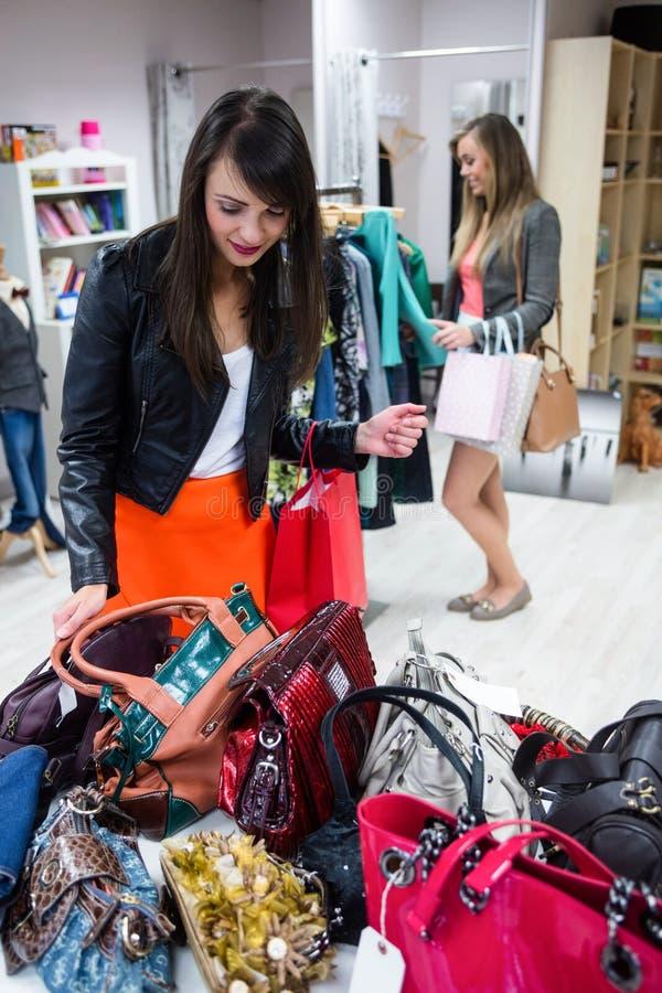 Femmes sélectionnant des sacs et des vêtements tout en faisant des emplettes photo stock
