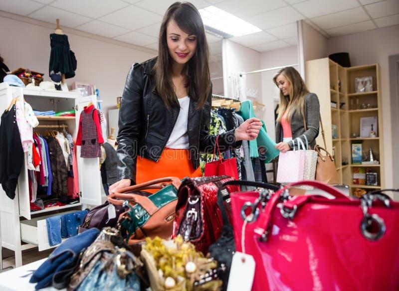 Femmes sélectionnant des sacs et des vêtements tout en faisant des emplettes photos libres de droits