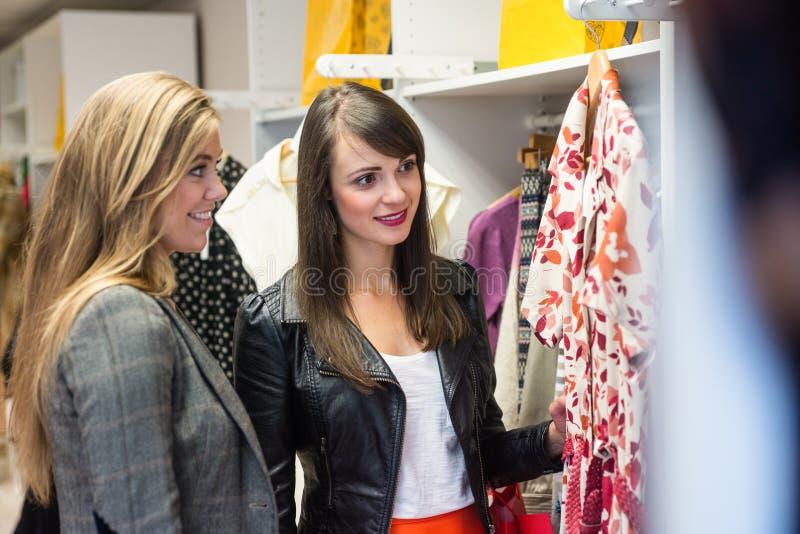 Femmes sélectionnant une robe tout en faisant des emplettes pour des vêtements photographie stock libre de droits