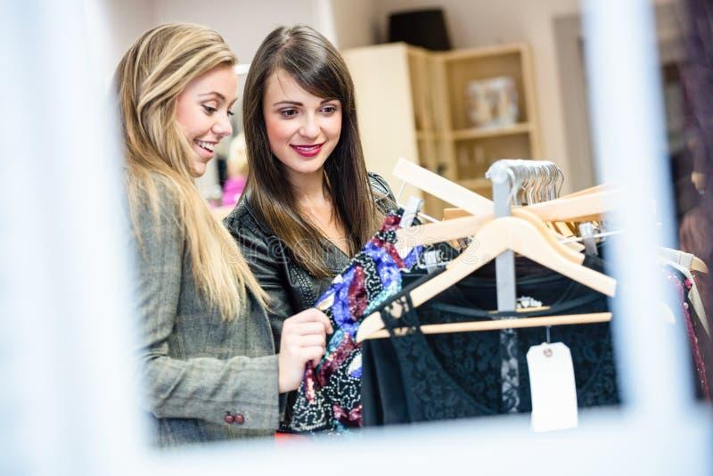 Femmes sélectionnant une robe tout en faisant des emplettes pour des vêtements photos stock
