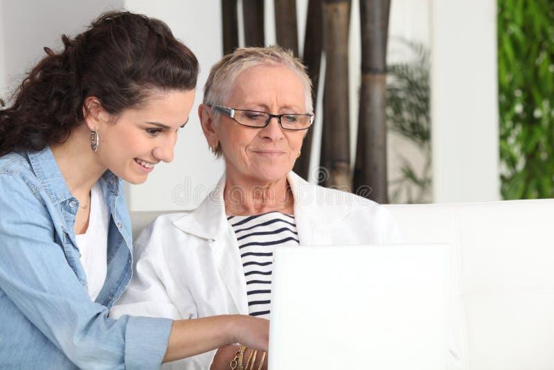 Femmes s'asseyant à un ordinateur portatif photographie stock