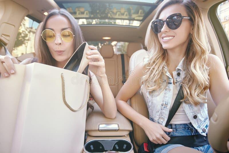 Femmes s'asseyant dans la voiture après l'achat photographie stock
