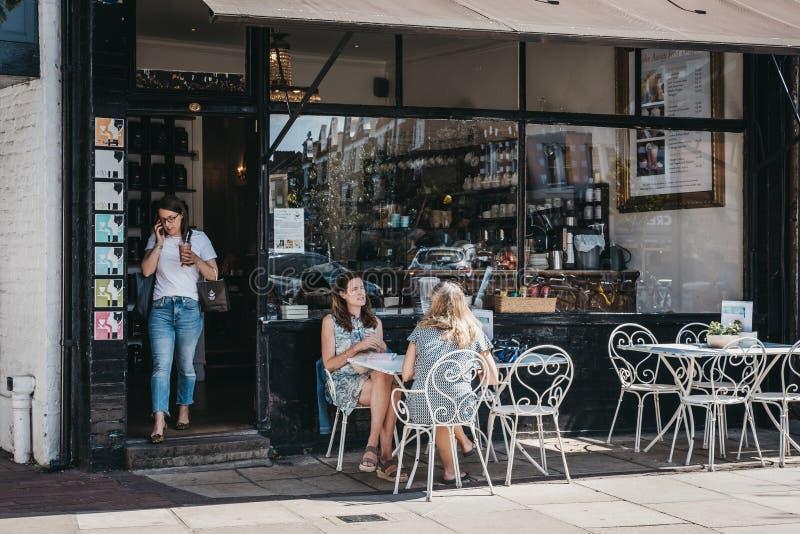 Femmes s'asseyant et causant à une table extérieure d'un café dans la grange photo stock