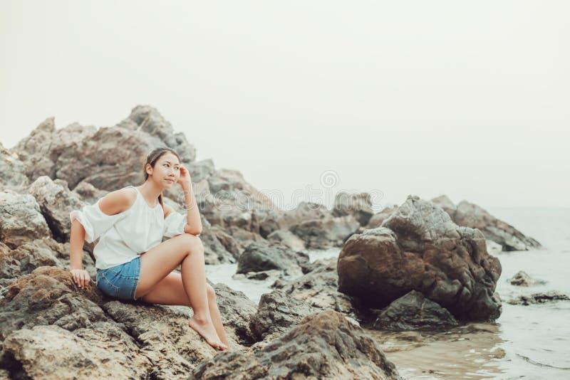 Femmes s'asseyant sur la pierre près de la plage entre le voyage photographie stock