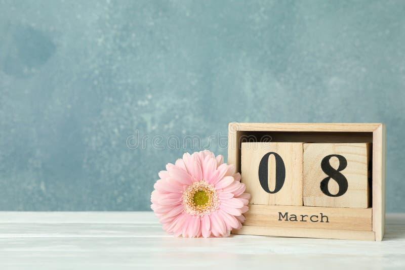 Femmes ` s jour 8 mars avec le calendrier de bloc en bois Jour de mères heureux Fleur de ressort sur la table blanche photographie stock