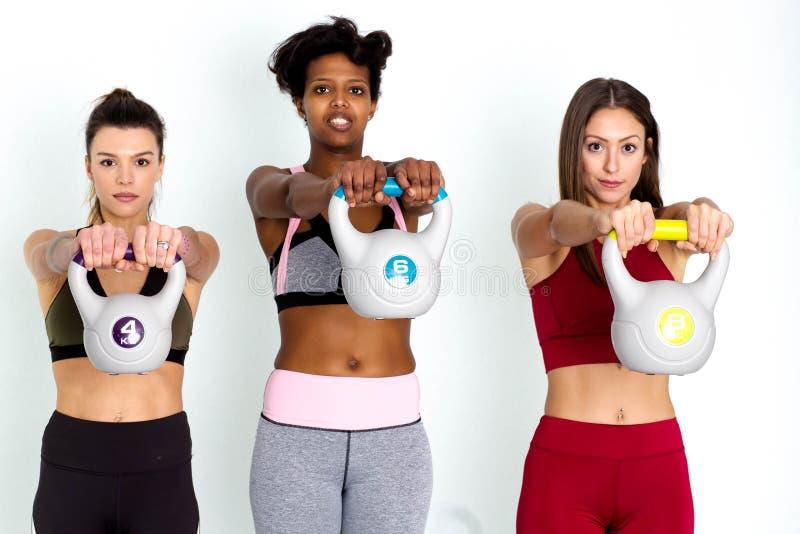 Femmes soulevant des kettlebells à Groupe d'athlètes féminins soulevant des kettlebells - image photos stock