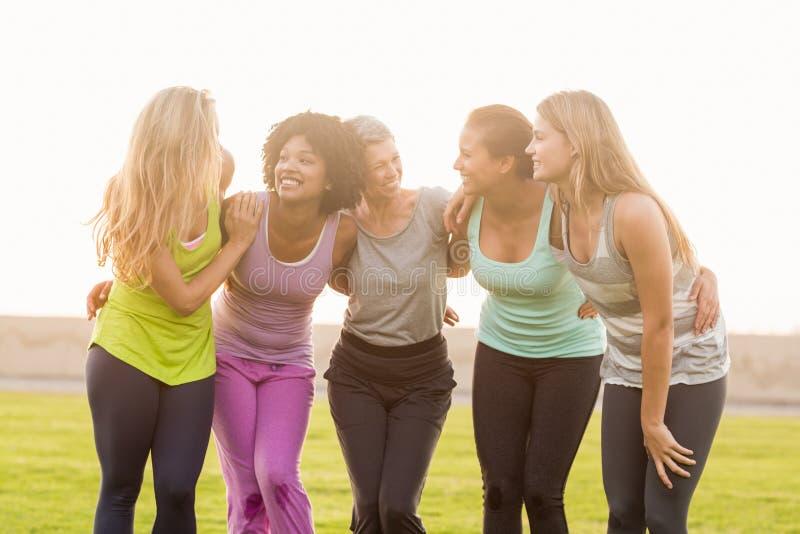 Femmes sportives de sourire avec des bras autour de l'un l'autre photos stock