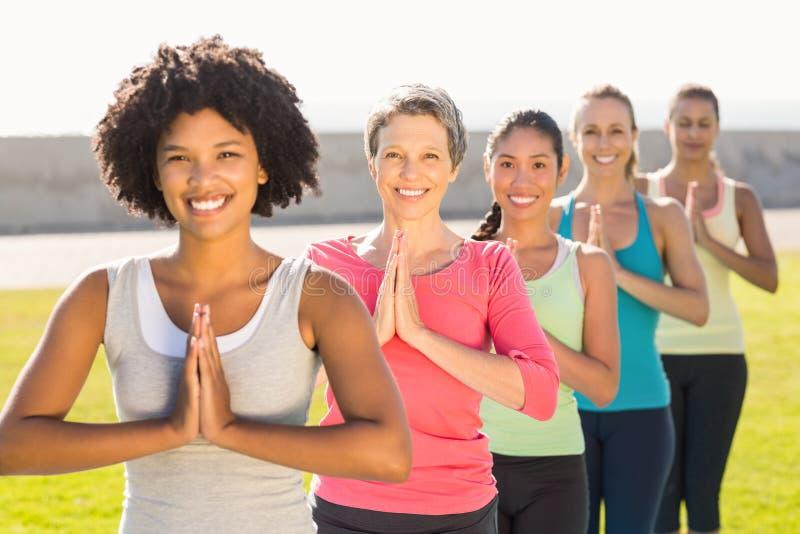 Femmes sportives de sourire faisant la position de prière dans la classe de yoga images stock