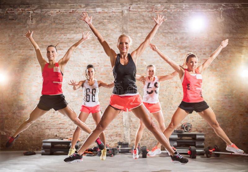 Femmes sportives faisant l'exercice sautant photo stock