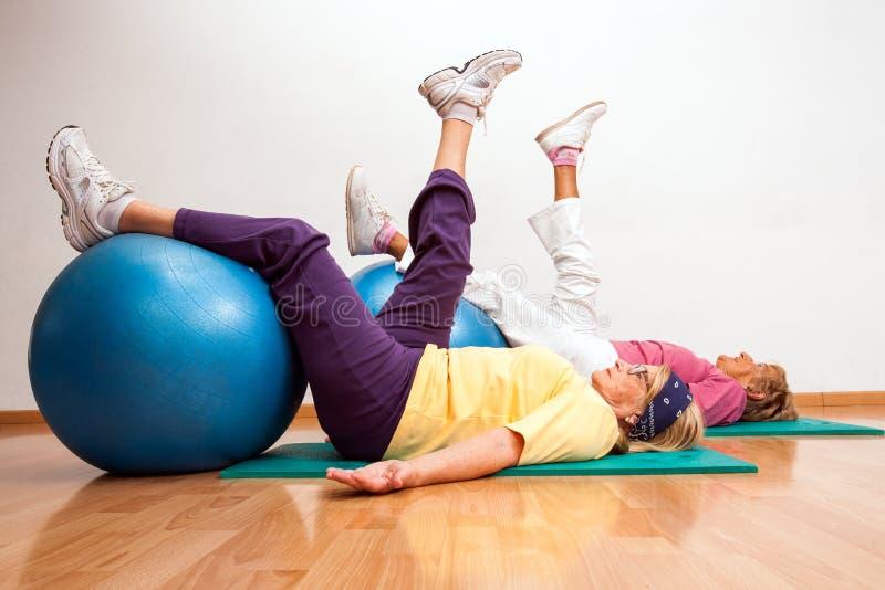Femmes supérieures établissant avec des boules de forme physique photo stock