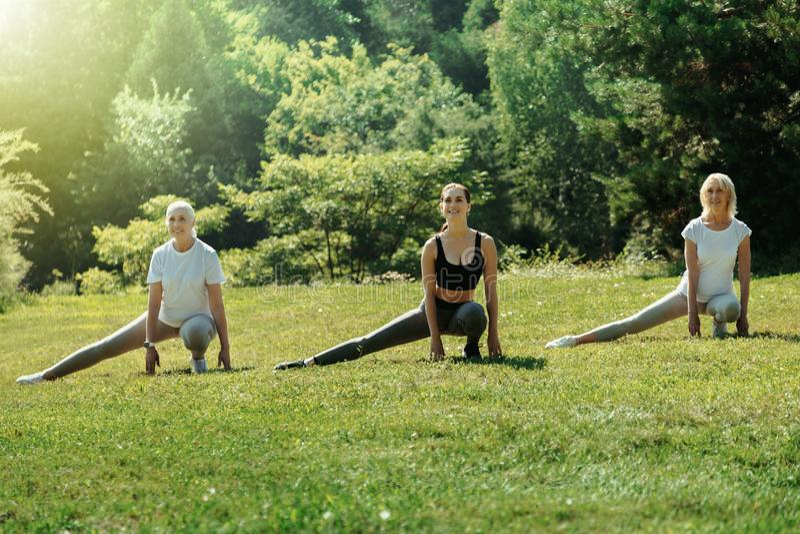 Femmes supérieures actives et jeune entraîneur étirant leurs jambes photos stock