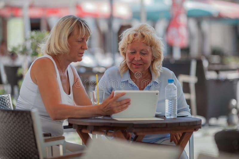 Femmes supérieures détendant en café et à l'aide du comprimé numérique images libres de droits