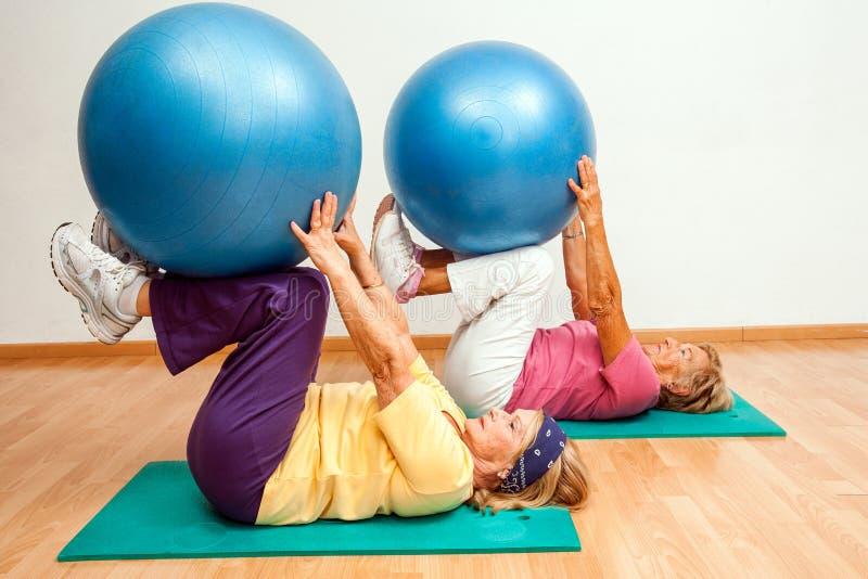 Femmes supérieures s'exerçant avec des boules de gymnase image libre de droits