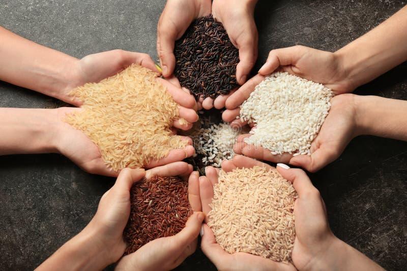 Femmes tenant différents types de riz sur le fond gris, vue supérieure images libres de droits