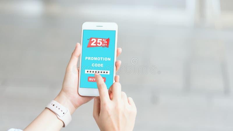 Femmes tenant le smartphone pour écrire le code pour obtenir une remise du magasin image libre de droits