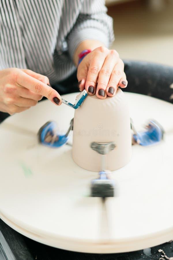Femmes travaillant à la roue de potier dedans le studio, tasse en céramique photos libres de droits