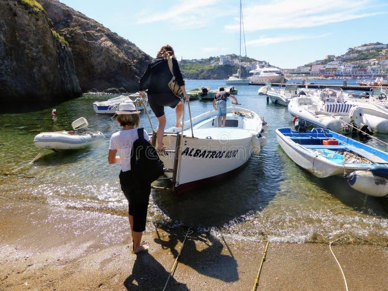 Femmes vues par derrière monter dans un petit bateau pour un voyage de bateau en île de Ponza en Italie images libres de droits