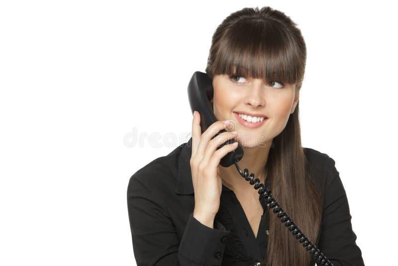Femmina al posto di lavoro che comunica sul telefono immagine stock